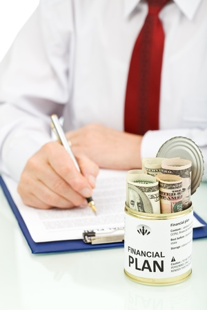 Business man making financial plan with an opened can of US dollars Stock Photo - 9986984