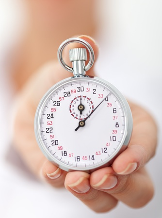 stop time: Stopwatch in womans hand - closeup, shallow depth
