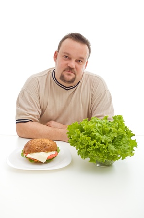ponder: Diet choices concept - man with hamburger and lettuce at the table, isolated