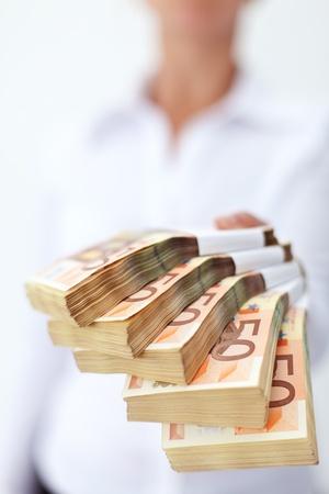 mucho dinero: Pila de billetes en euros entregado a ti - profundidad