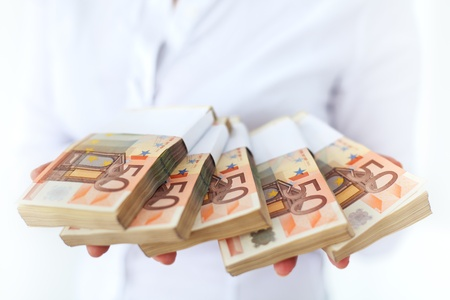 50 euro: Lots of money in stacks - european currency in woman hands, shallow depth