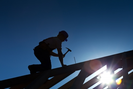roof top: Builder or carpenter working on the roof - silhouette with strong back light