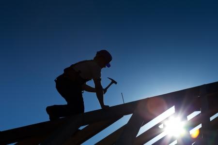 menuisier: Builder ou charpentier travaillant sur le toit - silhouette avec forte lumi�re arri�re Banque d'images