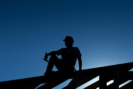 Builder or carpenter resting on top of roof structure - silhouette with strong back light