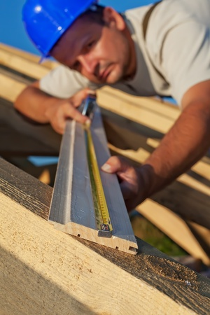 planck: Builder carpenter measuring wood planck looking closely - shallow depth, focus on foreground Stock Photo