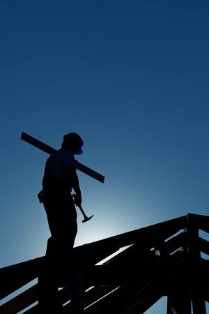 Builder working late on top of building holding hammer - in strong back light