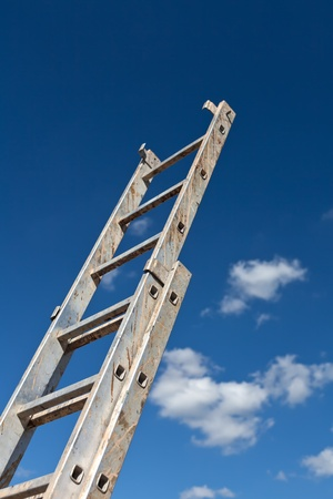 Dirty ladder pointing to the sky and some clouds photo