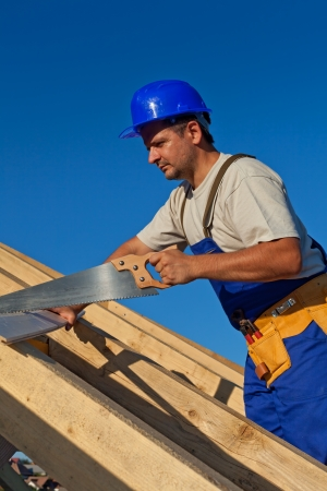 carpenter tools: Carpenter working on the roof with a saw Stock Photo