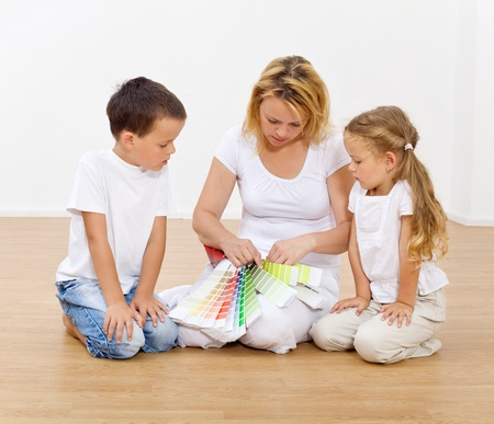 Choosing the colors in our new home - woman and kids with color chart Stock Photo - 10733071