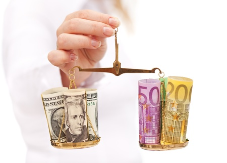 Currency rate risk concept - woman hand with euro and dollar on balance photo