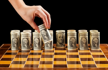 international investments: Money strategies concept - dollar bills on chess board manipulated by woman hand