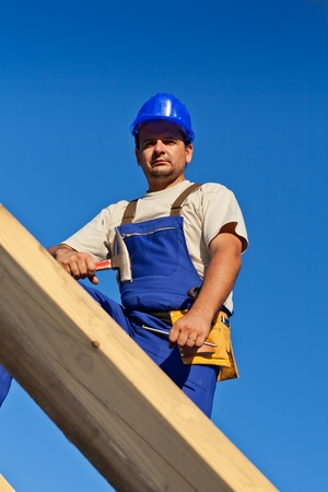 stubble: Carpenter worker on top of wooden structure looking down