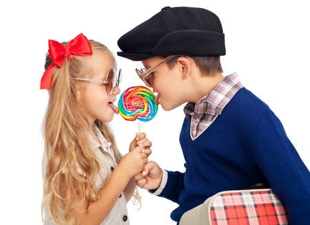 Love is sharing - childhood sweethearts with a lollipop and vintage clothes photo