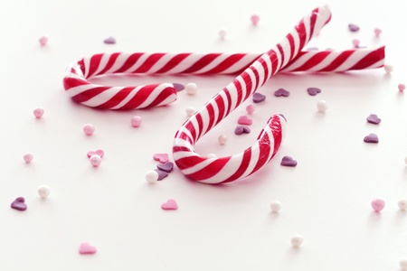 scattered on white background: Christmas candy sticks and scattered sweets on white surface