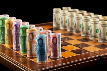Euros and dollars on chess board - closeup Stock Photo