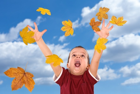 Happy boy shouting and reaching out for the falling autumn leaves -  without motion blur photo