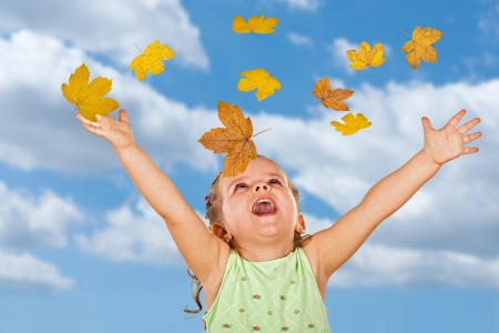 Happy shouting little girl welcoming the falling autumn leaves against cloudy sky photo