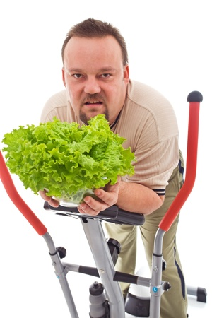 combined effort: Chubby man on trainer device holding lettuce in sheer disgust Stock Photo