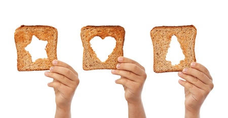Bread slices with christmas symbols cutouts in child hands - help concept, isolated photo