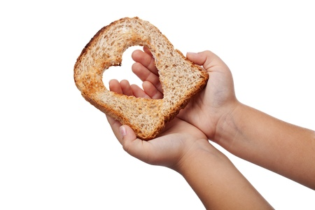 needy: Giving food with love concept - slice of bread in child hands, isolated