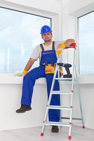 mounting: Handyman or worker resting after work leaning on the windowsill Stock Photo
