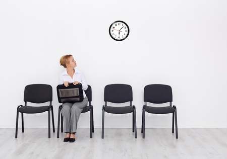 check room: Still waiting for the job interview - woman checking time Stock Photo