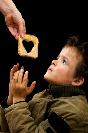 poverty relief: Feeding the poor concept with dirty kid receiving slice of bread - on black Stock Photo