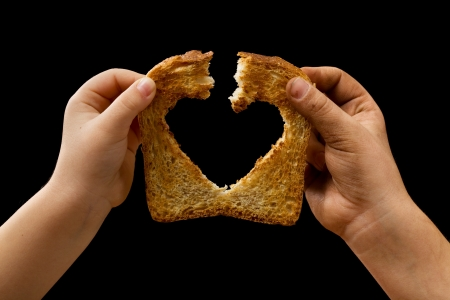 needy: Sharing food with love - kids hands breaking a slice of bread
