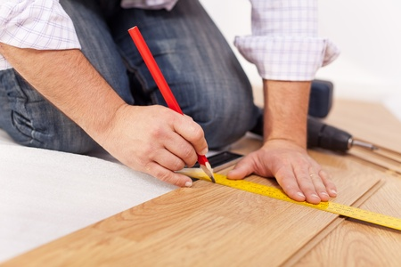 improvment: Home improvment - laying laminate flooring, measuring Stock Photo