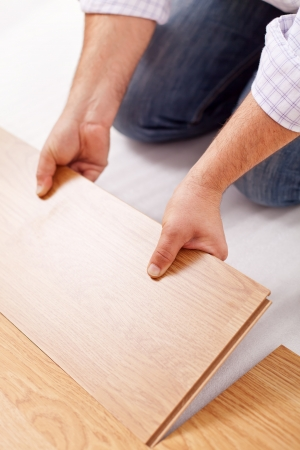 Home improvement - installing laminate flooring, fitting a plank 免版税图像