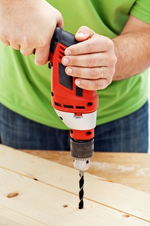 Carpenter or joiner working - drilling hole in wood, closeup