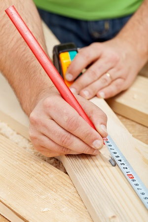 Carpenter or joiner measuring wood and marking with pencil - closeup photo