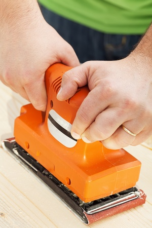 joiner: Man chiseling wood with sander power tool - closeup Stock Photo