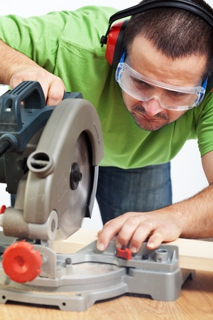 Carpenter or joiner working with power tool - cutting wood photo