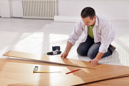 laminate flooring: Home improvement - man laying new laminate flooring in empty room