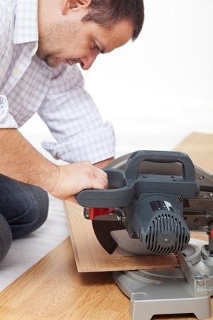 Home improvement - cutting the laminate flooring planks, focus on hand photo
