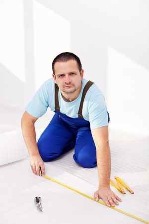 Worker laying isolating foam layer beneath flooring - measuring and cutting Stock Photo - 11891181