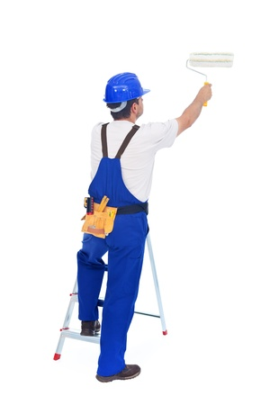 roller brush: Handyman or worker painting with roller brush leaning on ladder - back view, isolated Stock Photo