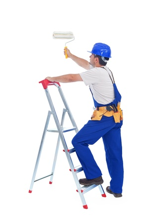 ladder safety: Handyman or worker painting with roller brush standing on ladder - isolated with a bit of shadow Stock Photo