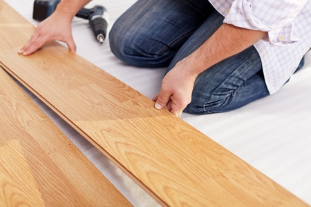 in layers: Installing laminate flooring fitting the next piece - focus on hand
