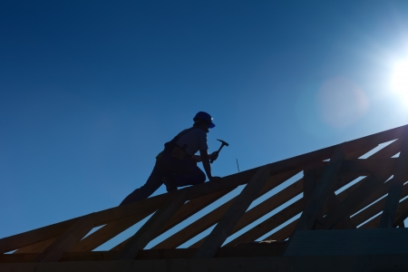 carpenter tools: Carpenter working on top of the roof wooden structure - strong backlight silhouette