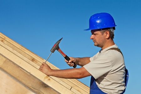 roof work: Carpenter working on the roof wooden structure - driving in big nail