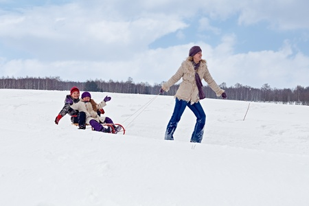 Children sleigh riding - their mother pulling in winter landscape photo