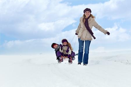 trineo: Los niños se divierten en un trineo en la nieve con su madre Foto de archivo