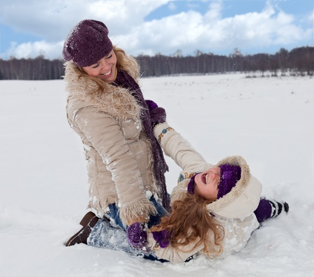 exhilarated: Woman and little girl having fun in the snow on a beautiful winter day