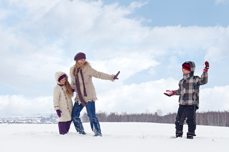 family fight: Kids and woman enjoy the snow having a snowball fight Stock Photo