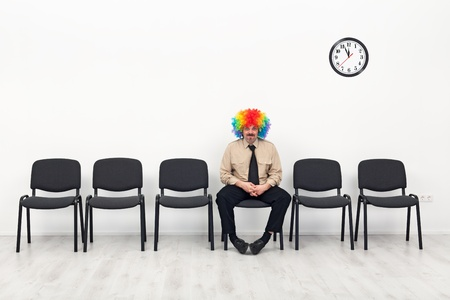 impatient: Last man standing - waiting concept with clown in business outfit