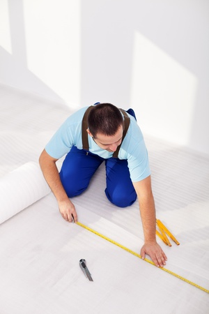 Laying laminate flooring at home - measuring and cutting the isolation layer photo