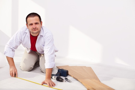 Man installing laminate flooring at home - the isolation layer photo