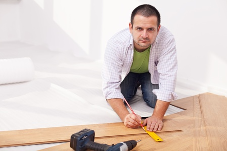 Installing laminate flooring - man working on the floor photo